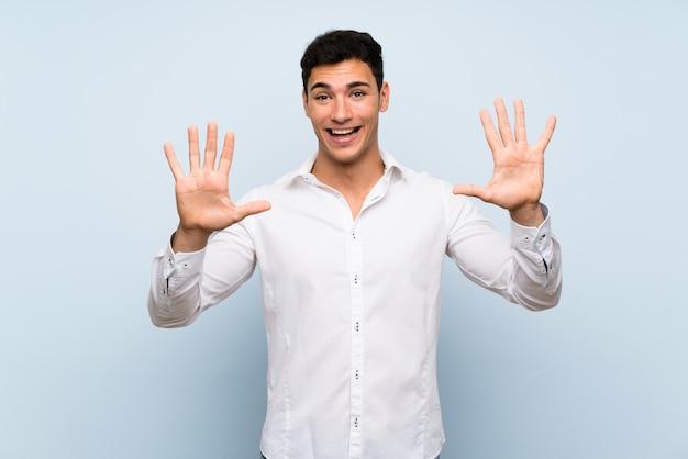 Przystojny mężczyzna nad błękitną ścianą liczy dziesięć z palcami