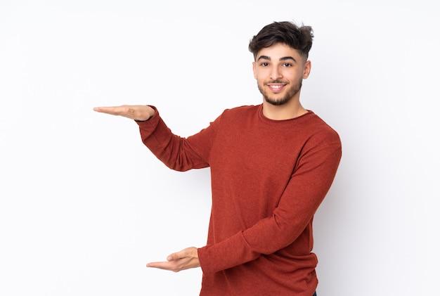 Przystojny mężczyzna nad izolowane ściany gospodarstwa copyspace do wstawienia reklamy