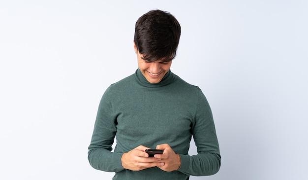 Przystojny mężczyzna nad niebieską ścianą, wysyłanie wiadomości z telefonu komórkowego