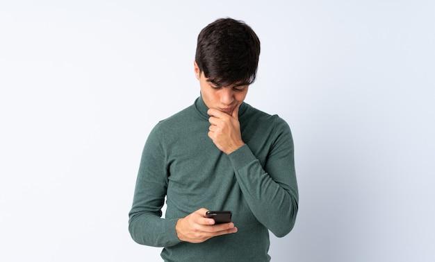 Przystojny mężczyzna nad niebieski ściany myślenia i wysyłanie wiadomości