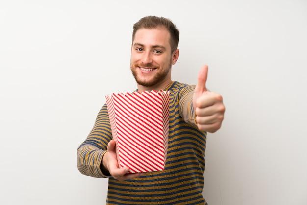 Przystojny mężczyzna nad odosobnioną biel ścianą trzyma puchar popkorny