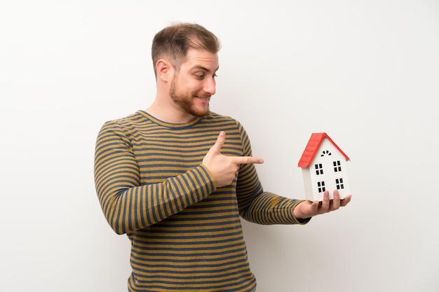 Przystojny mężczyzna nad odosobnioną biel ścianą trzyma troszkę dom