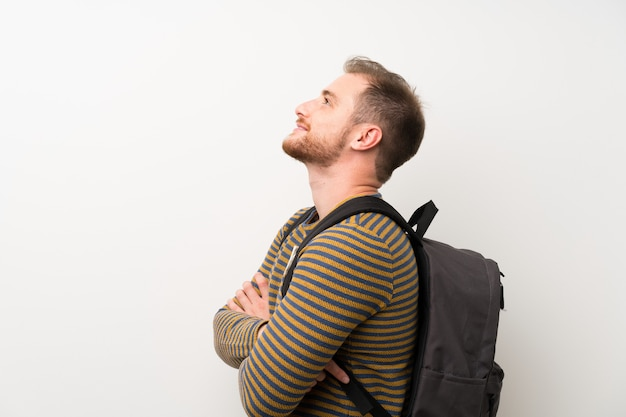 Przystojny mężczyzna nad odosobnioną biel ścianą z plecakiem