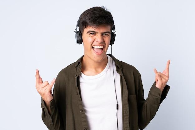 Przystojny mężczyzna nad odosobnioną błękitną słuchającą muzyką robi rockowemu gestowi