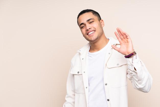 Przystojny mężczyzna nad odosobnioną ścianą salutuje z ręką z szczęśliwym wyrażeniem