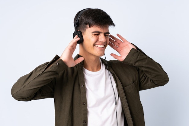 Przystojny mężczyzna nad odosobnionym błękitnym tła słuchającą muzyką i śpiewem