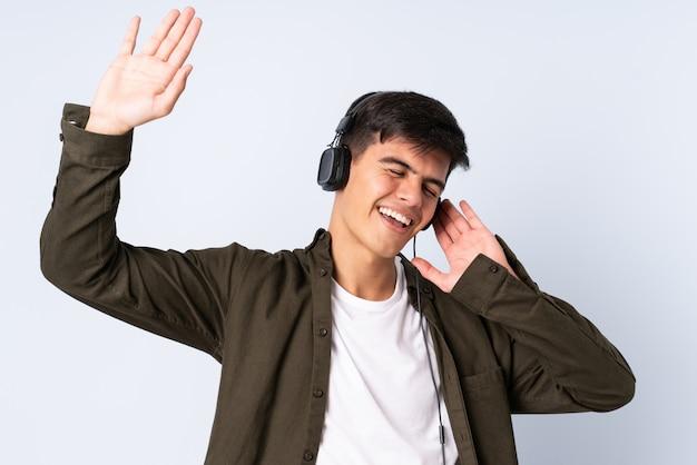 Przystojny mężczyzna nad odosobnionym błękitnym tła słuchającą muzyką i tanem