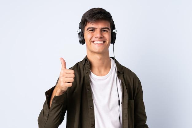 Przystojny mężczyzna nad odosobnionym błękitnym tła słuchającą muzyką z kciukiem up i