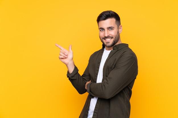 Przystojny mężczyzna nad odosobnionym kolorem żółtym