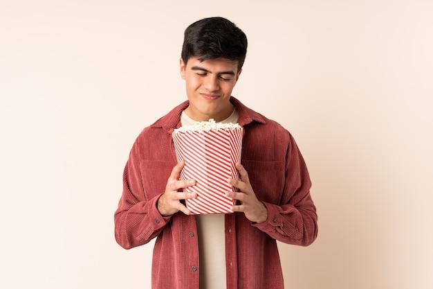 Przystojny mężczyzna nad ścianą trzyma duże wiadro popcorns