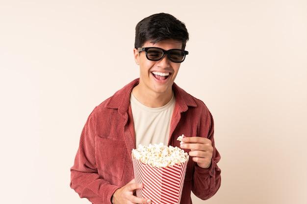 Przystojny mężczyzna nad ścianą w okularach 3d i gospodarstwa duże wiadro popcorns, wskazując z przodu