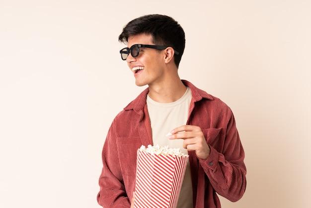 Przystojny mężczyzna nad ścianą w okularach 3d i gospodarstwa duże wiadro popcorns