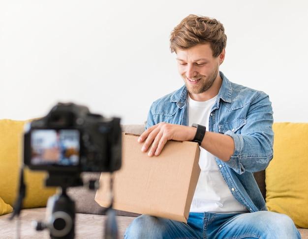 Przystojny mężczyzna nagrywający podczas rozpakowywania produktu