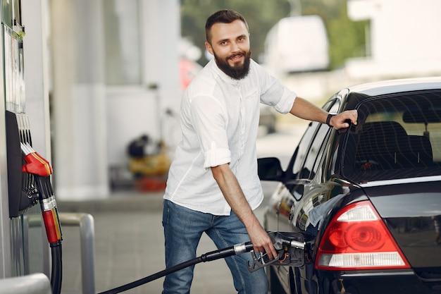 Przystojny mężczyzna nalewa benzynę do zbiornika samochodu