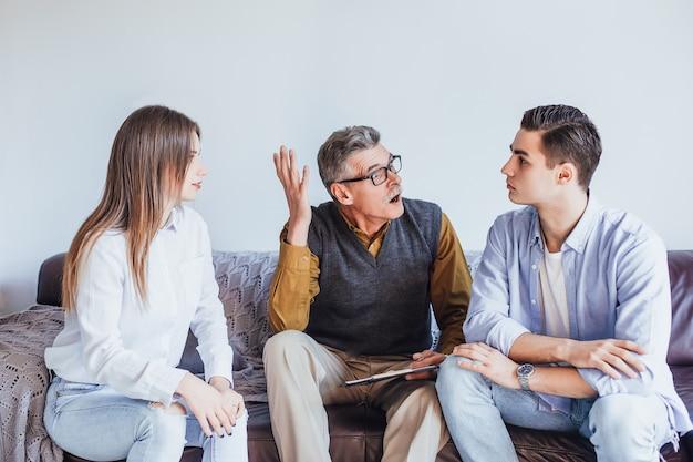 Przystojny mężczyzna nieszczęśliwy siedzi z żoną na kanapie na terapii z psychologiem