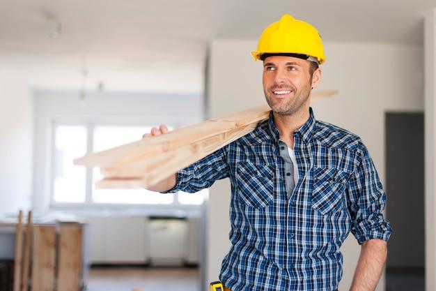 Przystojny mężczyzna niosący deski drewniane
