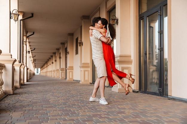 Przystojny mężczyzna niosący kobietę w rękach i uśmiechający się podczas spaceru w pobliżu pięknego budynku
