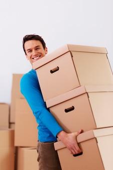 Przystojny mężczyzna niosący stos pudełek