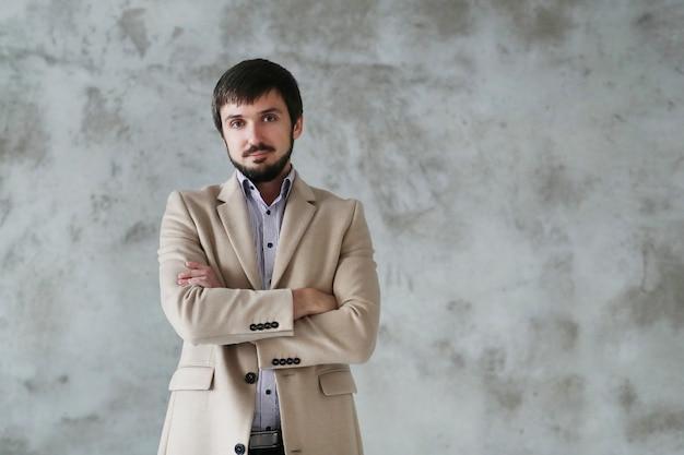 Przystojny mężczyzna nosi beżowy płaszcz