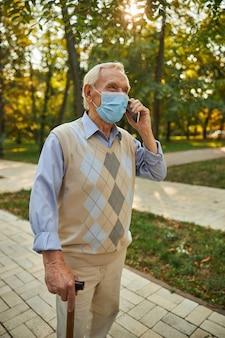 Przystojny mężczyzna noszący maskę ochronną leku odpoczywający na świeżym powietrzu