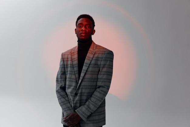 Przystojny mężczyzna o afrykańskim wyglądzie w szarej kurtce moda na białym tle