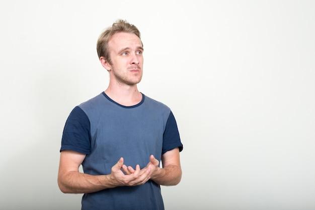 Przystojny mężczyzna o blond włosach na białej ścianie