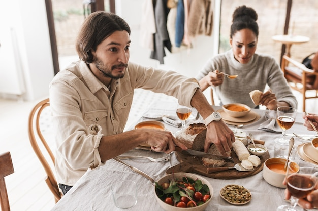 Przystojny mężczyzna o ciemnych włosach i brodzie siedzi przy stole rozmarzonym krojeniu chleba