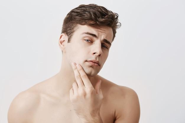 Przystojny mężczyzna o ciemnych włosach, stylowej fryzurze, niebieskich oczach, trzyma rękę na brodzie, wygląda zamyślony, odizolowany. pewny siebie nagi europejczyk o czystej i zdrowej skórze