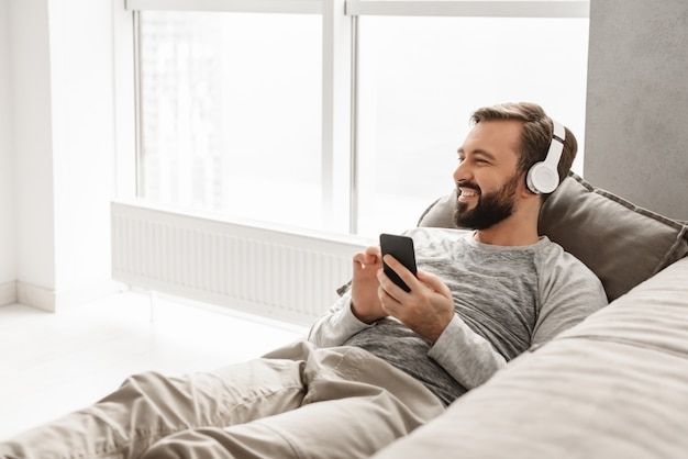 Przystojny mężczyzna o europejskim wyglądzie w podstawowym ubraniu leżący na kanapie w domu i słuchający muzyki za pomocą czarnego telefonu komórkowego w słuchawkach bezprzewodowych
