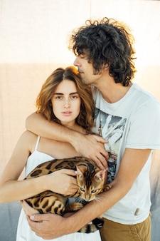 Przystojny mężczyzna o kręconych włosach delikatnie przytula swoją ukochaną. w rękach trzymają kota. w tle szara tkanina.