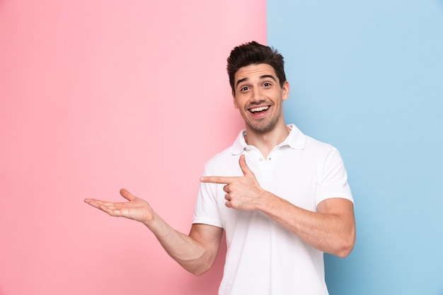 Przystojny mężczyzna o ściernisku wskazując palcami na bok na lato, na białym tle nad kolorową ścianą