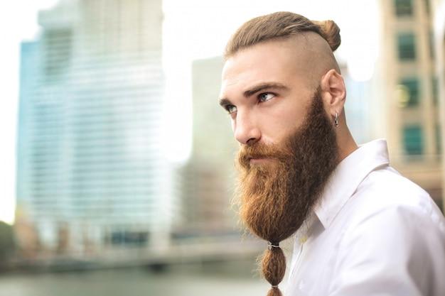 Przystojny mężczyzna o stylowych długich włosach i długiej brodzie