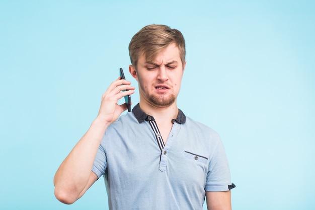Przystojny mężczyzna o zmęczonym i poirytowanym spojrzeniu odsuwa telefon od ucha