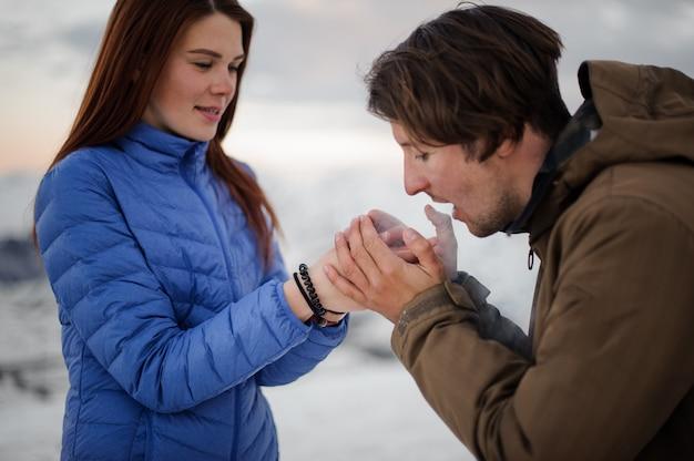 Przystojny mężczyzna ocieplenie jego ręce dziewczyny z oddychaniem w górach