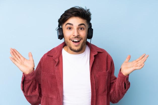 Przystojny mężczyzna odizolowywający na błękit ścianie zaskakującej i słuchającej muzyki