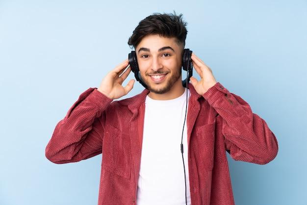 Przystojny mężczyzna odizolowywający na błękit ściany słuchającej muzyce
