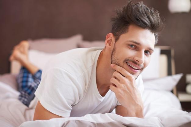 Przystojny mężczyzna odpoczywa rano na łóżku