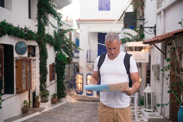 Przystojny mężczyzna patrząc na mapę miasta na wycieczkę