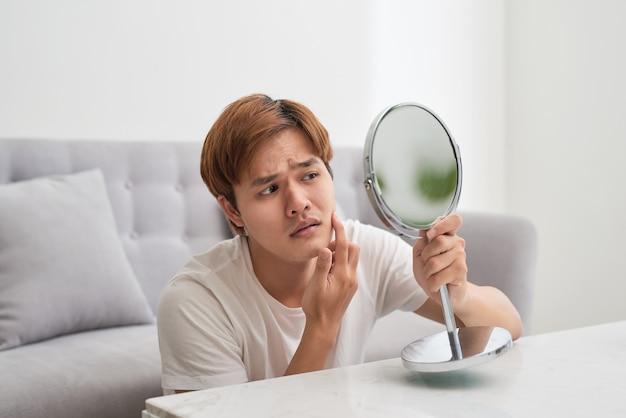 Przystojny mężczyzna patrząc na siebie w lustrze. wyciskanie pryszcz.