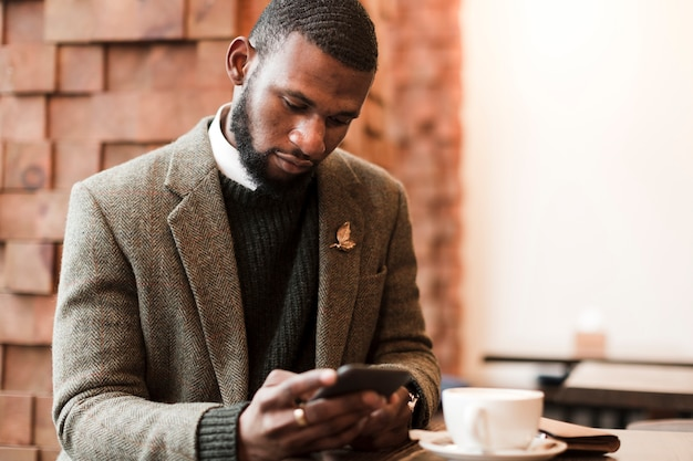Przystojny mężczyzna patrzeje na jego telefonie indoors w szarej kurtce