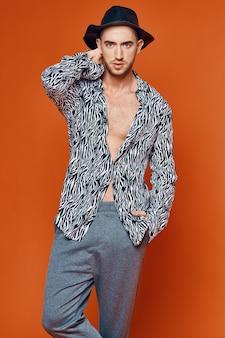 Przystojny mężczyzna pewności siebie pomarańczowym tle studio model