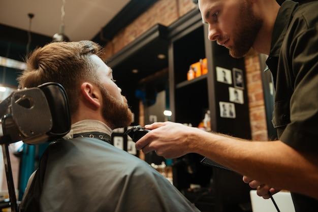 Przystojny mężczyzna pierwsze strzyżenie brody przez fryzjera siedząc na krześle u fryzjera.