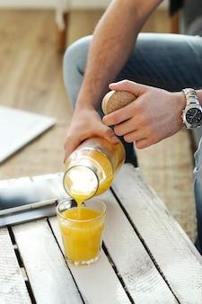 Przystojny mężczyzna pije sok pomarańczowy