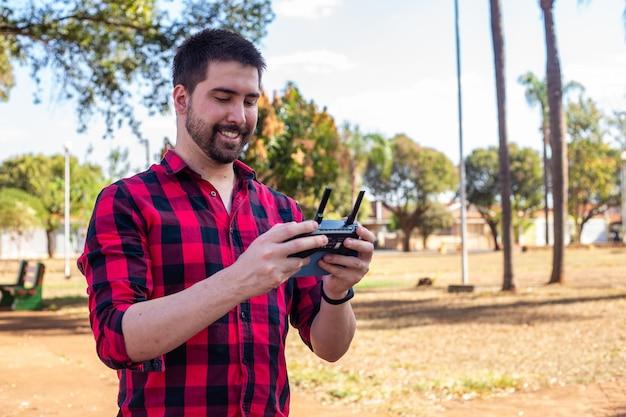 Przystojny mężczyzna pilotuje drona na placu. młody chłopak z pilotem filmowanie za pomocą drona.