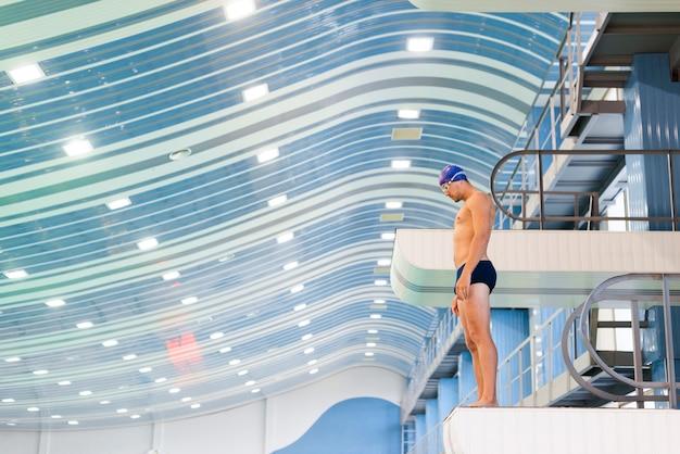 Przystojny mężczyzna pływak przygotowuje się do skoku