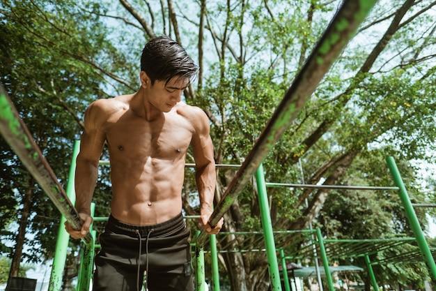 Przystojny mężczyzna podciąga się, aby poprawić wydolność płuc i schudnąć, ćwicząc na świeżym powietrzu w parku