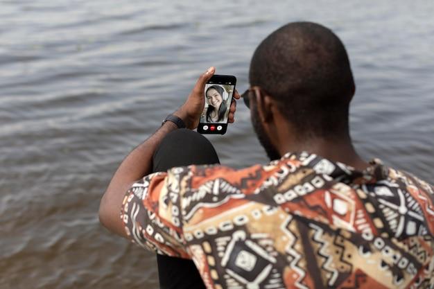 Przystojny mężczyzna podczas rozmowy wideo z nowoczesnym smartfonem na zewnątrz