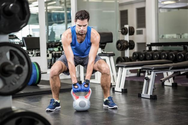 Przystojny mężczyzna podnoszenia kettlebell na siłowni