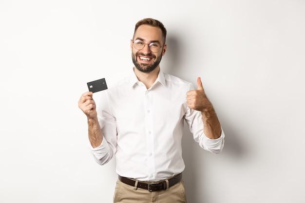 Przystojny mężczyzna pokazując swoją kartę kredytową i kciuk w górę, rekomendując bank, stojąc kopiowanie miejsca