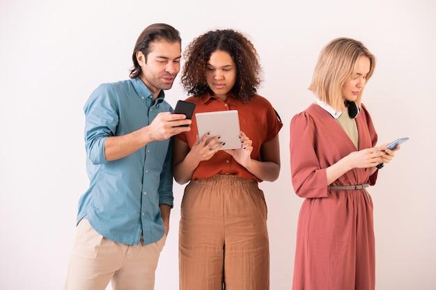Przystojny mężczyzna pokazujący aplikację na smartfona afroamerykańskiej dziewczynie z tabletem, omawiając z nią funkcje nowej aplikacji mobilnej